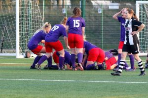 Wymondham Town Ladies congratulating each other on their semi-final cup win
