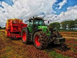 Tractor in a field showing farmer harvesting